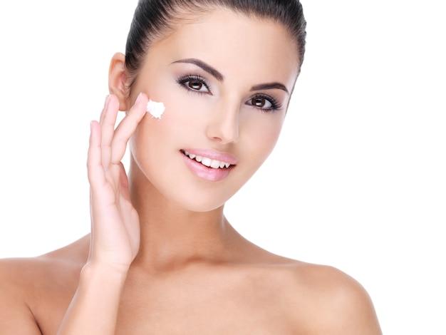 Młoda uśmiechnięta kobieta z kremem kosmetycznym na całkiem świeżej twarzy - na białym tle