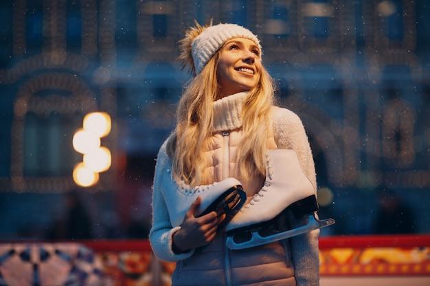 Młoda uśmiechnięta kobieta z łyżwami na lodowym lodowisku