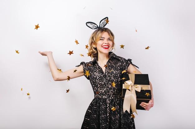 Młoda uśmiechnięta kobieta z pudełkiem na prezent, świętująca jasne wydarzenie, przyjęcie urodzinowe, nosi elegancką czarną sukienkę. musujące złote konfetti, zabawa, taniec.