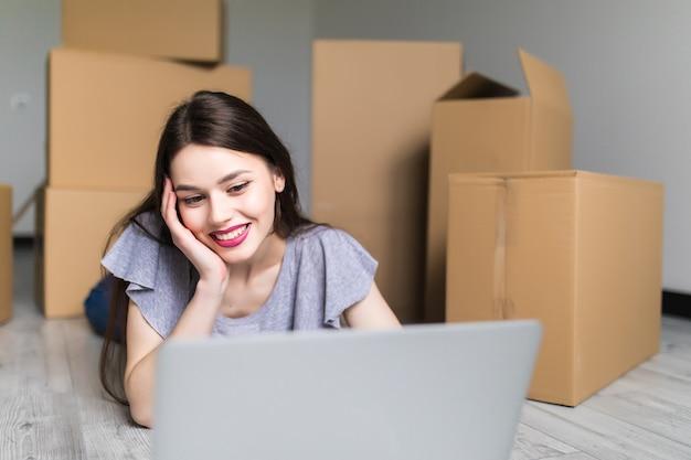 Młoda uśmiechnięta kobieta za pomocą laptopa w nowym domu, szukając mistrza naprawy, miejsca kopiowania, koncepcji ruchu