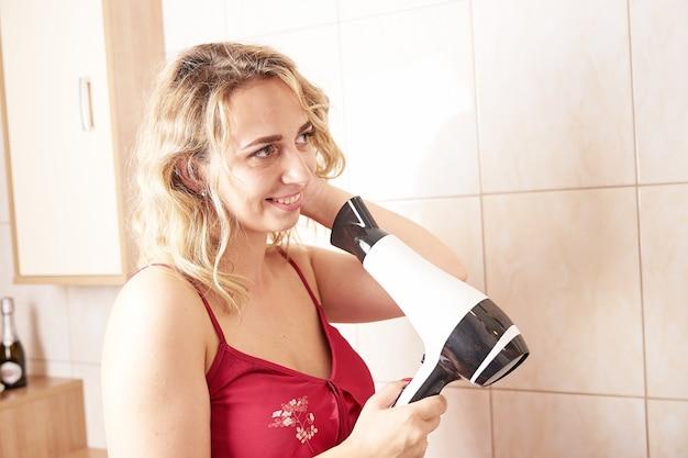 Młoda uśmiechnięta kobieta za pomocą suszarki do włosów i patrząc w mirrow podczas porannej rutyny