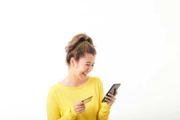Młoda uśmiechnięta kobieta za pomocą telefonu i numeru karty kredytowej na zakupy w internecie