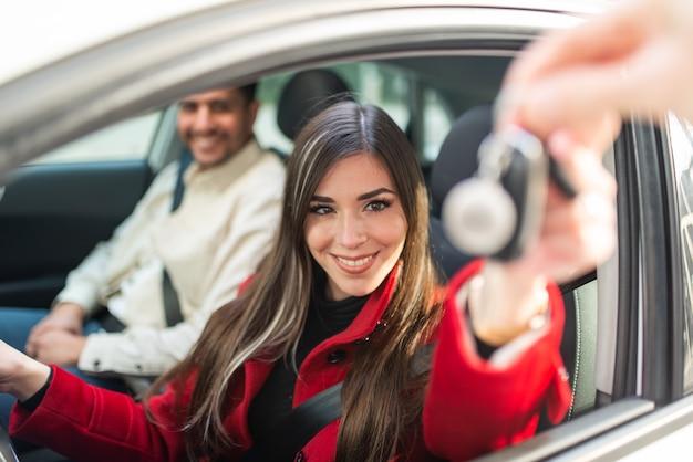 Młoda uśmiechnięta kobieta zabierająca kluczyki do samochodu