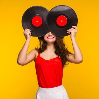 Młoda uśmiechnięta kobieta zamyka twarz z płyt winylowych. koncepcja zabawny dj