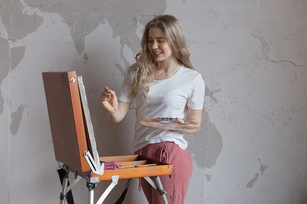 Młoda uśmiechnięta ładna blondynki dziewczyna z muśnięciem i paletą stoi blisko sztaluga rysunku obrazka
