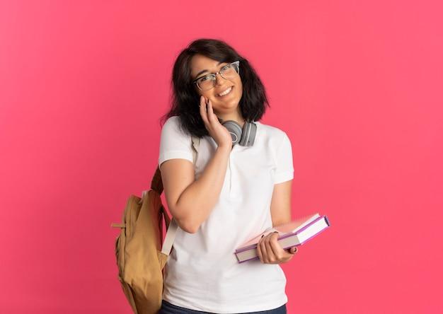 Młoda uśmiechnięta ładna kaukaska uczennica w okularach i słuchawkach na szyi kładzie dłoń na twarzy, trzymając książkę i notatnik na różowo z miejscem na kopię