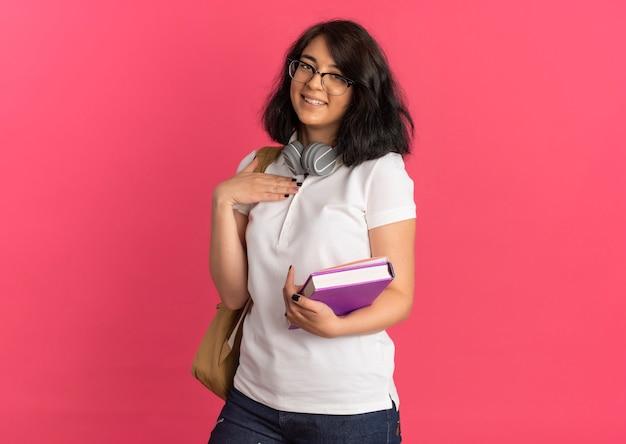 Młoda uśmiechnięta ładna kaukaska uczennica w okularach i słuchawkach na szyi trzyma książkę i notatnik kładzie rękę na piersi na różowo z miejscem na kopię