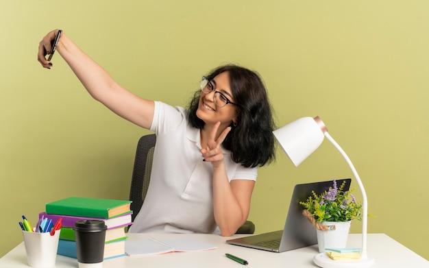 Młoda uśmiechnięta ładna kaukaska uczennica w okularach siedzi przy biurku z narzędziami szkolnymi gestami znak ręki zwycięstwa patrzy na telefon, biorąc selfie odizolowany na zielonej przestrzeni z miejscem na kopię