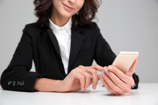 Młoda uśmiechnięta ładna kędzierzawa kobieta w czarnej kurtce siedzi i używa telefonu komórkowego