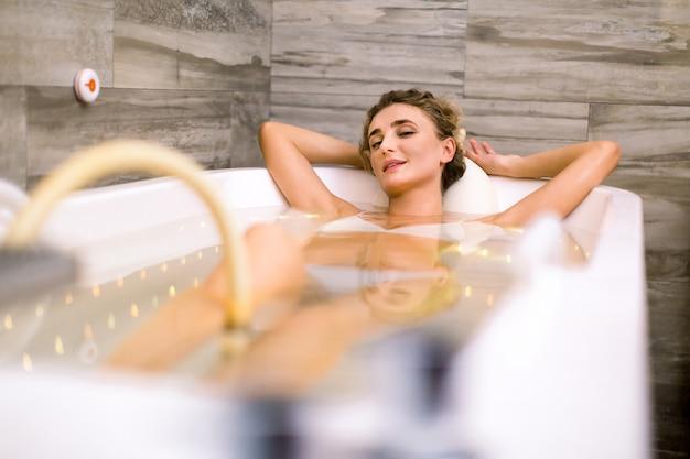 Młoda uśmiechnięta ładna kobieta w nowożytnej wannie podczas hydromasażu w piękno salonie