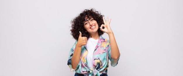 Młoda uśmiechnięta ładna kobieta z kręconymi włosami
