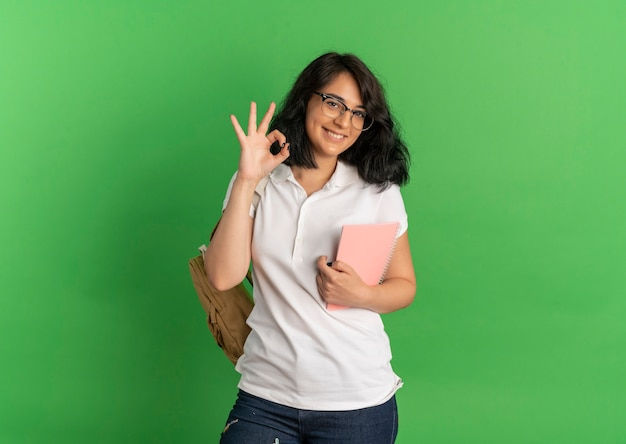 Młoda uśmiechnięta ładna uczennica kaukaska w okularach i z powrotem torbę gestykuluje ok ręka znak trzymając notebook na zielono z miejsca na kopię
