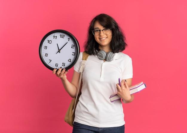 Młoda uśmiechnięta ładna uczennica kaukaska ze słuchawkami na szyi w okularach i torbie z tyłu posiada zegar i książki na różowo z miejsca na kopię