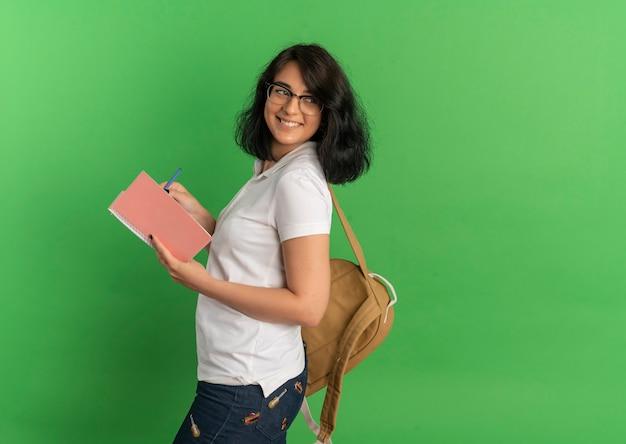 Młoda uśmiechnięta ładna uczennica kaukaski w okularach i plecak stoi bokiem trzymając długopis i notatnik na zielono z miejsca na kopię