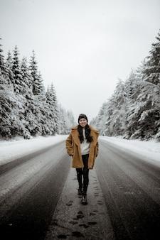 Młoda uśmiechnięta latynoska kobieta w stylowym płaszczu pozuje w malowniczym zimowym lesie