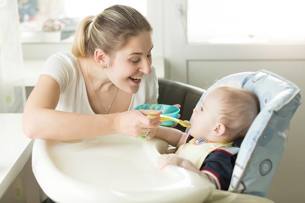 Młoda uśmiechnięta matka podająca sos jabłkowy swojemu dziecku w krzesełku