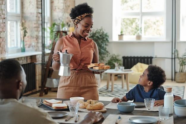 Młoda uśmiechnięta matka w stroju codziennym, podająca domowe gofry swojemu uroczemu synkowi, który będzie jadł śniadanie z rodzicami w kuchni