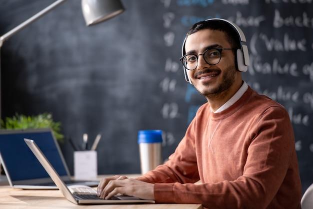 Młoda uśmiechnięta menedżer it z laptopem patrząc na ciebie podczas słuchania muzyki w słuchawkach podczas pracy w biurze