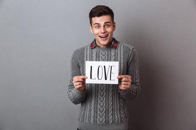 Młoda uśmiechnięta mężczyzna pozycja odizolowywająca mienie papier z miłość tekstem.