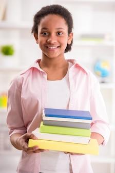 Młoda uśmiechnięta oliwkowa uczennicy mienia sterta książki.