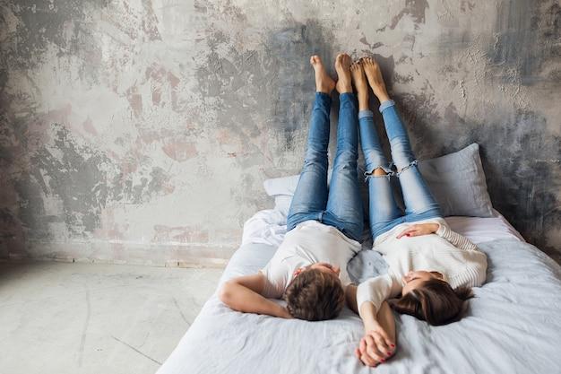 Młoda uśmiechnięta para leżąc na łóżku w domu w stroju casual