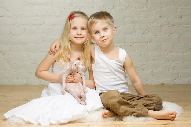 Młoda uśmiechnięta para - mała dziewczynka i chłopiec - z kociakiem sfinks