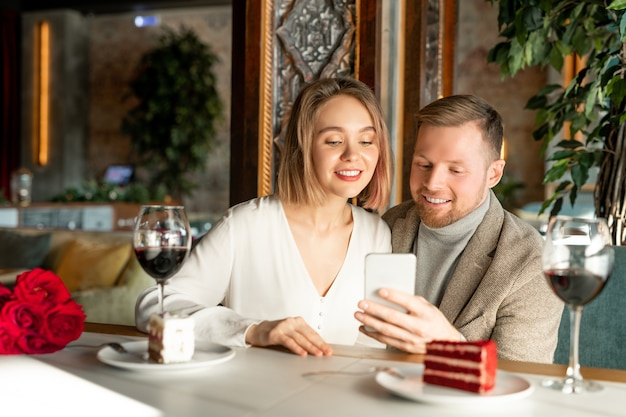 Młoda uśmiechnięta para ogląda coś w smartfonie, siedząc przy stole serwowanym w eleganckiej restauracji i mając wino i ciasta