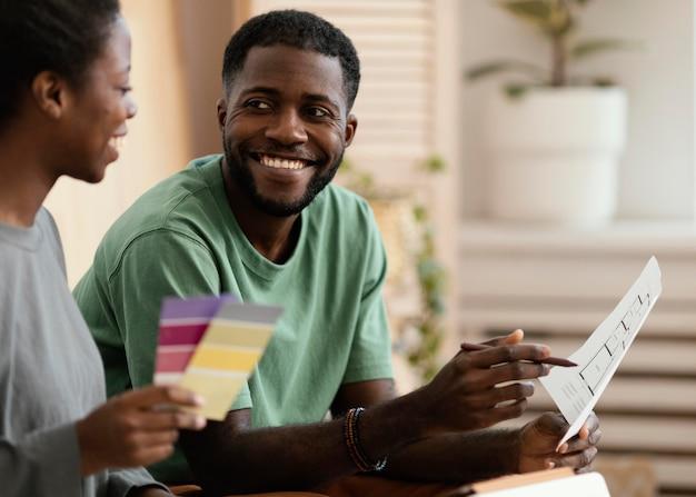 Młoda uśmiechnięta para robi plan przy użyciu palety kolorów do remontu domu