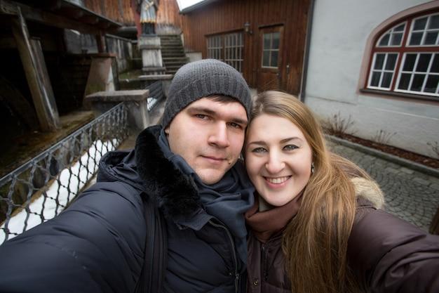 Młoda uśmiechnięta para robi selfie na ulicy w zimowy dzień