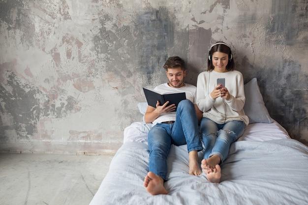 Młoda uśmiechnięta para siedzi na łóżku w domu w swobodnym stroju, czytając książkę w dżinsach, mężczyzna czytający książkę, kobieta słuchająca muzyki na słuchawkach, spędzający razem romantyczny czas
