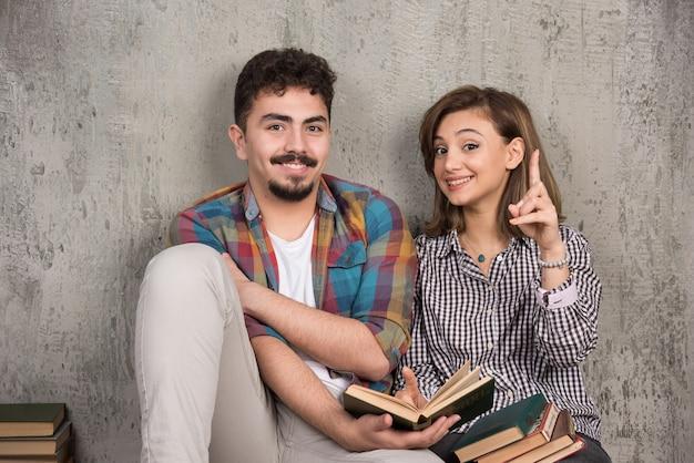 Młoda uśmiechnięta para siedzi na podłodze z książkami