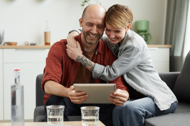 Młoda uśmiechnięta para siedzi o kanapie i patrząc na cyfrowy tablet rozmawiają z przyjaciółmi online w domu