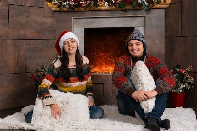 Młoda uśmiechnięta para w ciepłych swetrach i zabawnych czapkach zimowych siedząca na dywaniku przed udekorowanym kominkiem