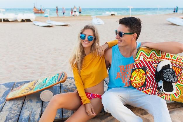 Młoda uśmiechnięta para zabawy na plaży z deską kitesurfingową na letnie wakacje