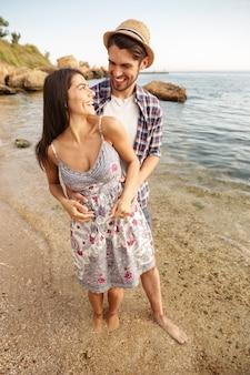 Młoda uśmiechnięta para zakochana stojąca na plaży i przytulająca się