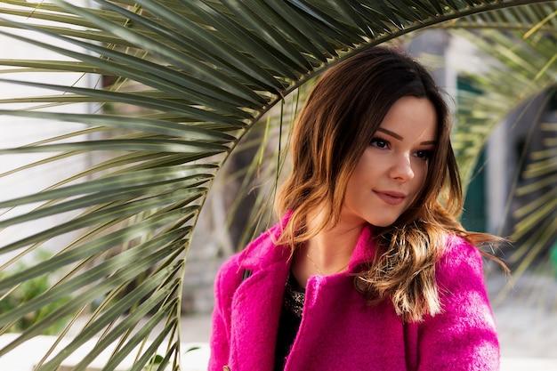 Młoda, uśmiechnięta piękna dziewczyna stoi w okularach obok palm na plaży. sam na sam z naturą.
