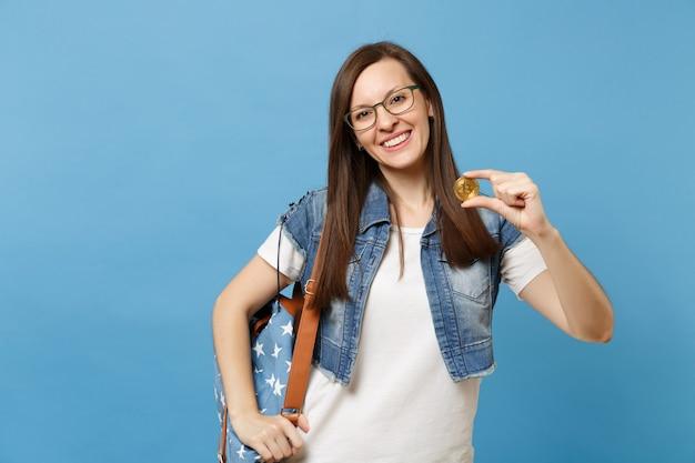 Młoda uśmiechnięta piękna kobieta studentka w okularach z plecakiem trzymając bitcoin, metalowe monety złotego koloru na białym tle na niebieskim tle. przyszła waluta. edukacja w liceum ogólnokształcącym.