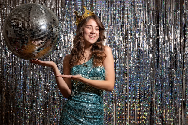 Młoda uśmiechnięta piękna pani ubrana w niebiesko-zieloną błyszczącą sukienkę z cekinami z koroną wskazującą coś po lewej stronie w partii
