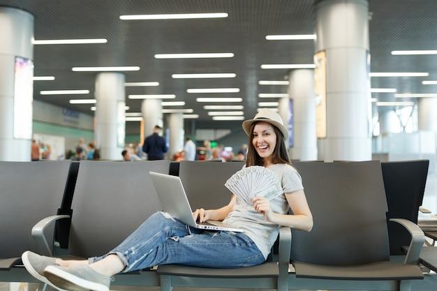 Młoda uśmiechnięta podróżniczka turystyczna kobieta pracująca na laptopie trzymaj pakiet dolarów gotówki czekaj w holu na międzynarodowym lotnisku