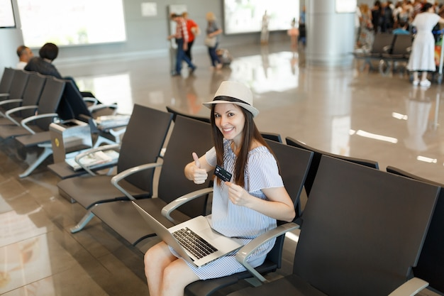 Młoda uśmiechnięta podróżniczka turystyczna kobieta pracująca na laptopie, trzymająca kartę kredytową, pokazująca kciuk w górę, czekająca w holu na międzynarodowym lotnisku