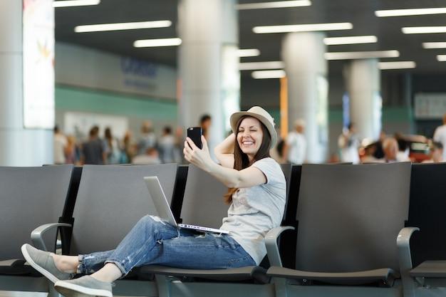 Młoda uśmiechnięta podróżniczka turystyczna kobieta pracuje na laptopie, robi selfie na telefonie komórkowym, czekając w holu na międzynarodowym lotnisku