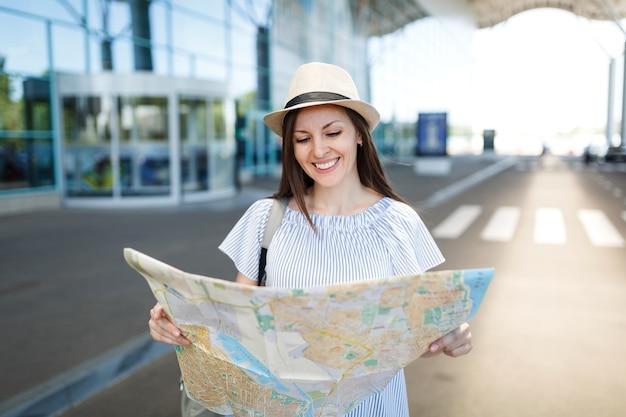 Młoda uśmiechnięta podróżniczka turystyczna kobieta w kapeluszu i lekkich ubraniach, trzymająca papierową mapę, stojąca na międzynarodowym lotnisku