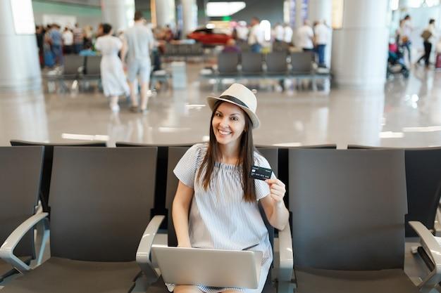 Młoda uśmiechnięta podróżniczka turystyczna kobieta w kapeluszu pracująca na laptopie, trzymająca kartę kredytową, czekająca w holu na międzynarodowym lotnisku