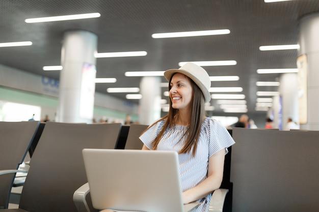 Młoda uśmiechnięta podróżniczka turystyczna kobieta w kapeluszu pracuje na laptopie podczas oczekiwania w holu na międzynarodowym lotnisku