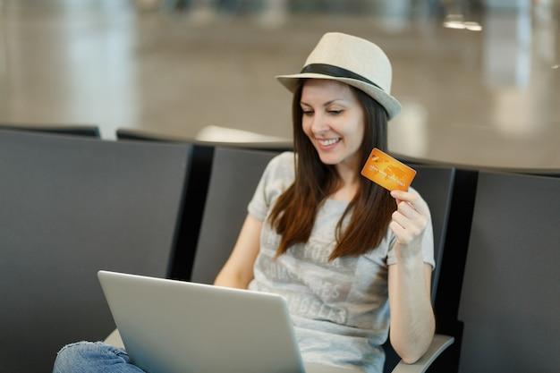 Młoda uśmiechnięta podróżniczka turystyczna kobieta w kapeluszu siedzi i pracuje na laptopie, trzymając kartę kredytową, czekając w holu na lotnisku