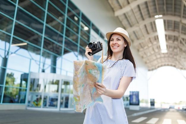 Młoda uśmiechnięta podróżniczka turystyczna kobieta w kapeluszu trzymająca retro vintage aparat fotograficzny, papierową mapę na międzynarodowym lotnisku