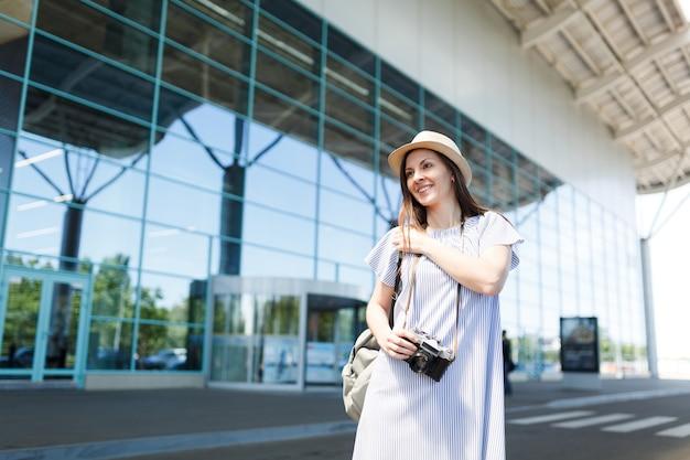 Młoda uśmiechnięta podróżniczka turystyczna kobieta w kapeluszu trzymająca retro vintage aparat fotograficzny, stojąca na międzynarodowym lotnisku