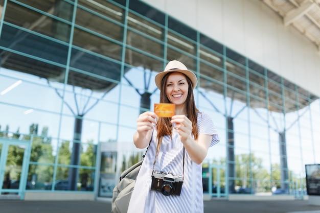 Młoda uśmiechnięta podróżniczka turystyczna kobieta w kapeluszu z plecakiem, retro vintage aparat fotograficzny, trzymająca kartę kredytową na międzynarodowym lotnisku