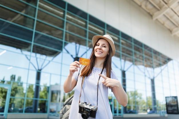 Młoda uśmiechnięta podróżniczka turystyczna kobieta z retro vintage aparatem fotograficznym, wskazując palcem wskazującym na karcie kredytowej na międzynarodowym lotnisku
