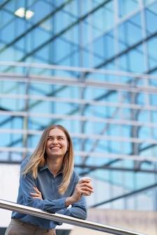 Młoda uśmiechnięta profesjonalna kobieta o przerwie na kawę podczas jej pełnego dnia pracy. trzyma papierowy kubek na zewnątrz w pobliżu budynku biznesowego, jednocześnie relaksując się i delektując napojem.